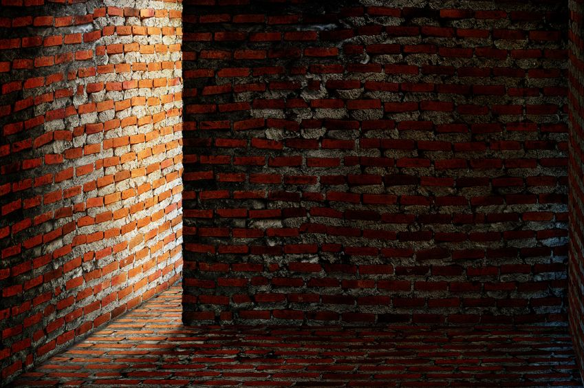 8912178 - dark brick room with light shining around a corner