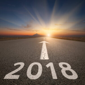 76650953 - empty highway leading to the mountains through the desert against the upcoming 2018 new year at beautiful sunrise. success concept.